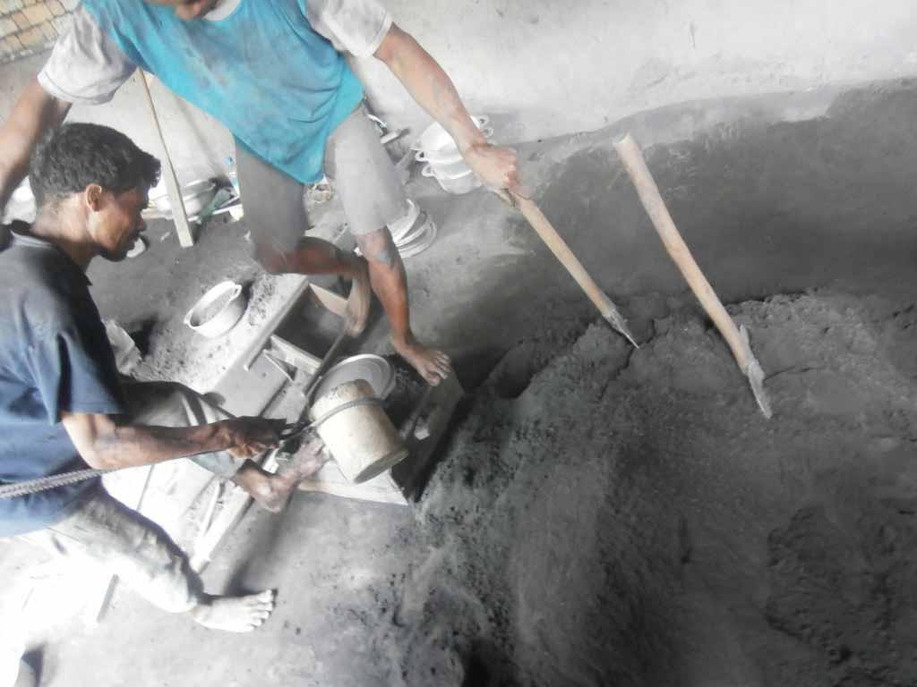 Les ouvriers sont en train de verser l'aluminium fondu dans la matrice
